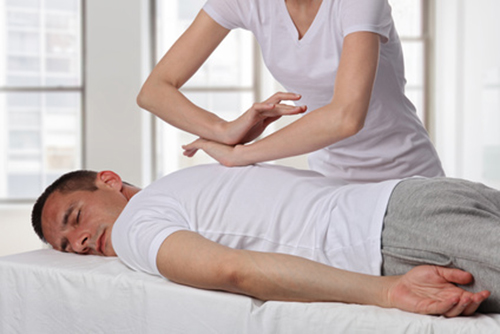 Manual therapy, Therapist doing healing treatment on man's back. Alternative medicine, pain relief concept. Shiatsu and Reiki in Kelowna, Canada